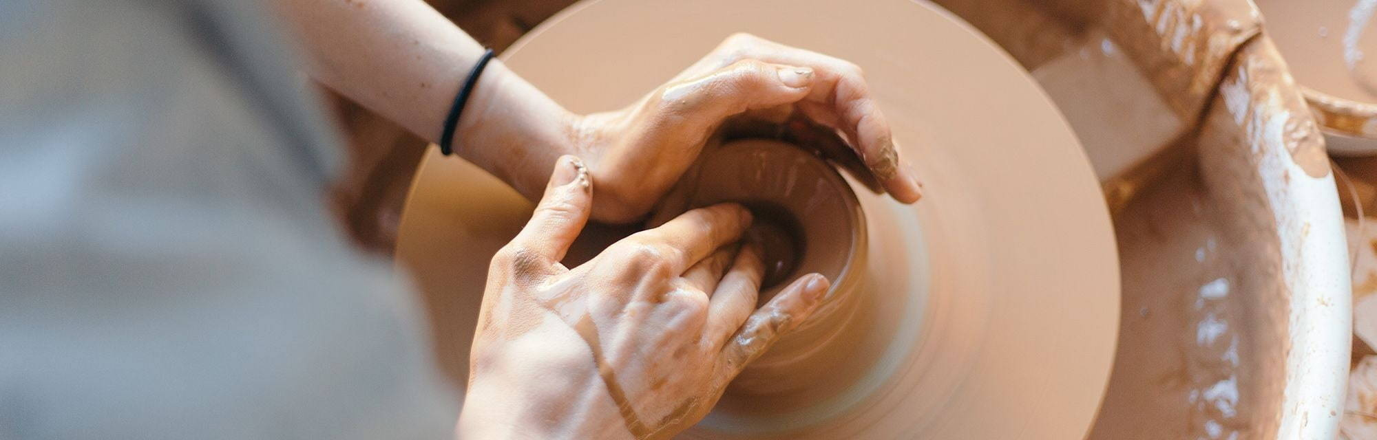 Hands at pottery wheel